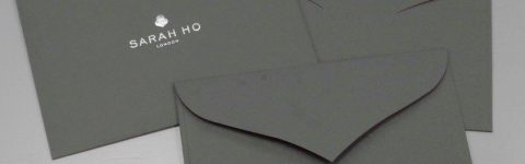 Bespoke tuck-flap curved diamond flap envelopes with silver foil print flat sheet conversion from GF Smith Dark Grey Colorplan Linen Embossed
